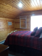 Second floor bedroom at Torch Lake Lodge. Features antique bed and view of fire pit.
