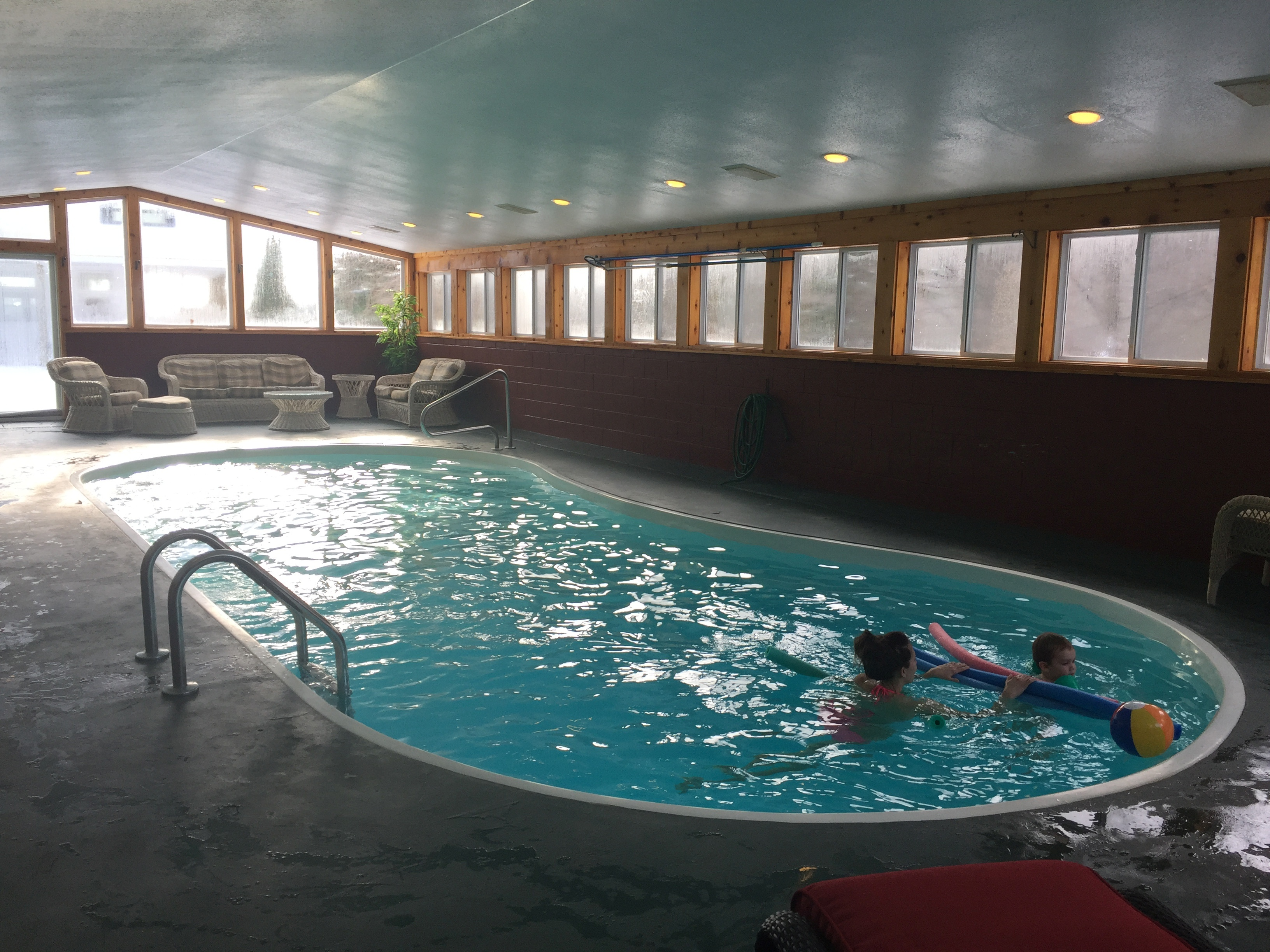 Indoor heated pool and seating at Torch Lake Lodge
