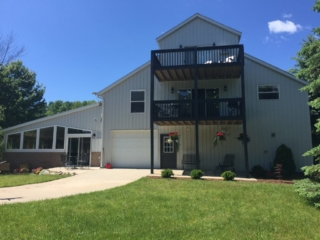 Front of Torch Lake lodge. Includes outdoor seating and table. Yard is available for games.