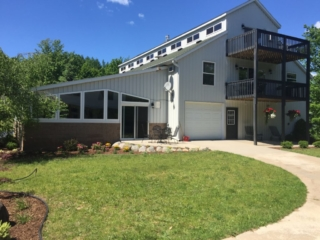 Another front view of Torch Lake lodge. Includes outdoor seating and table. Yard is available for games.