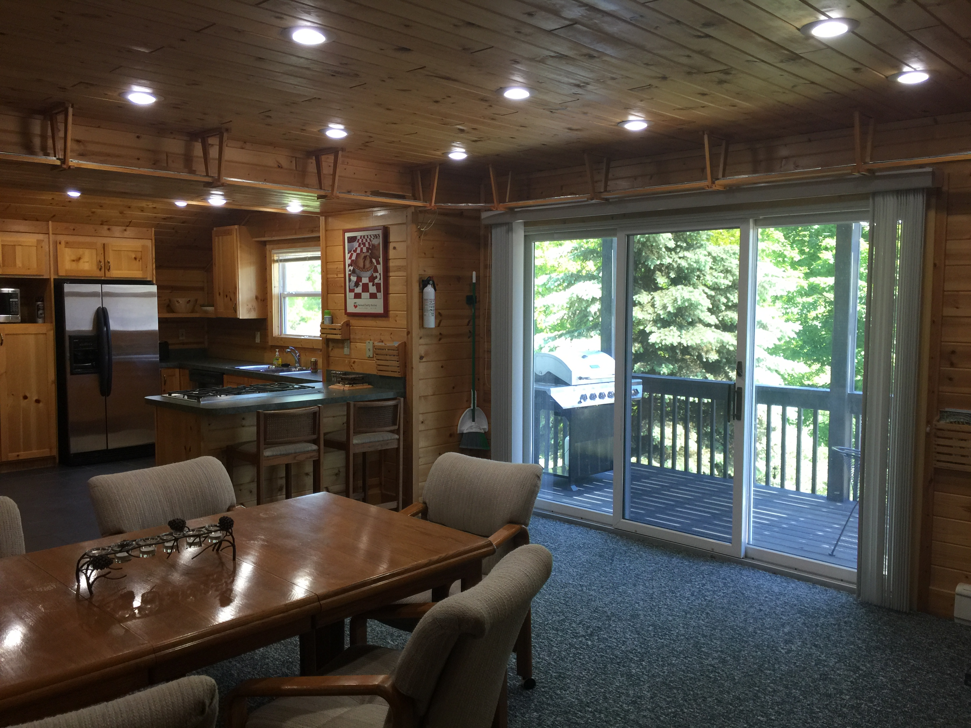 2nd floor deck with grill, chairs and table at Torch Lake Lodge