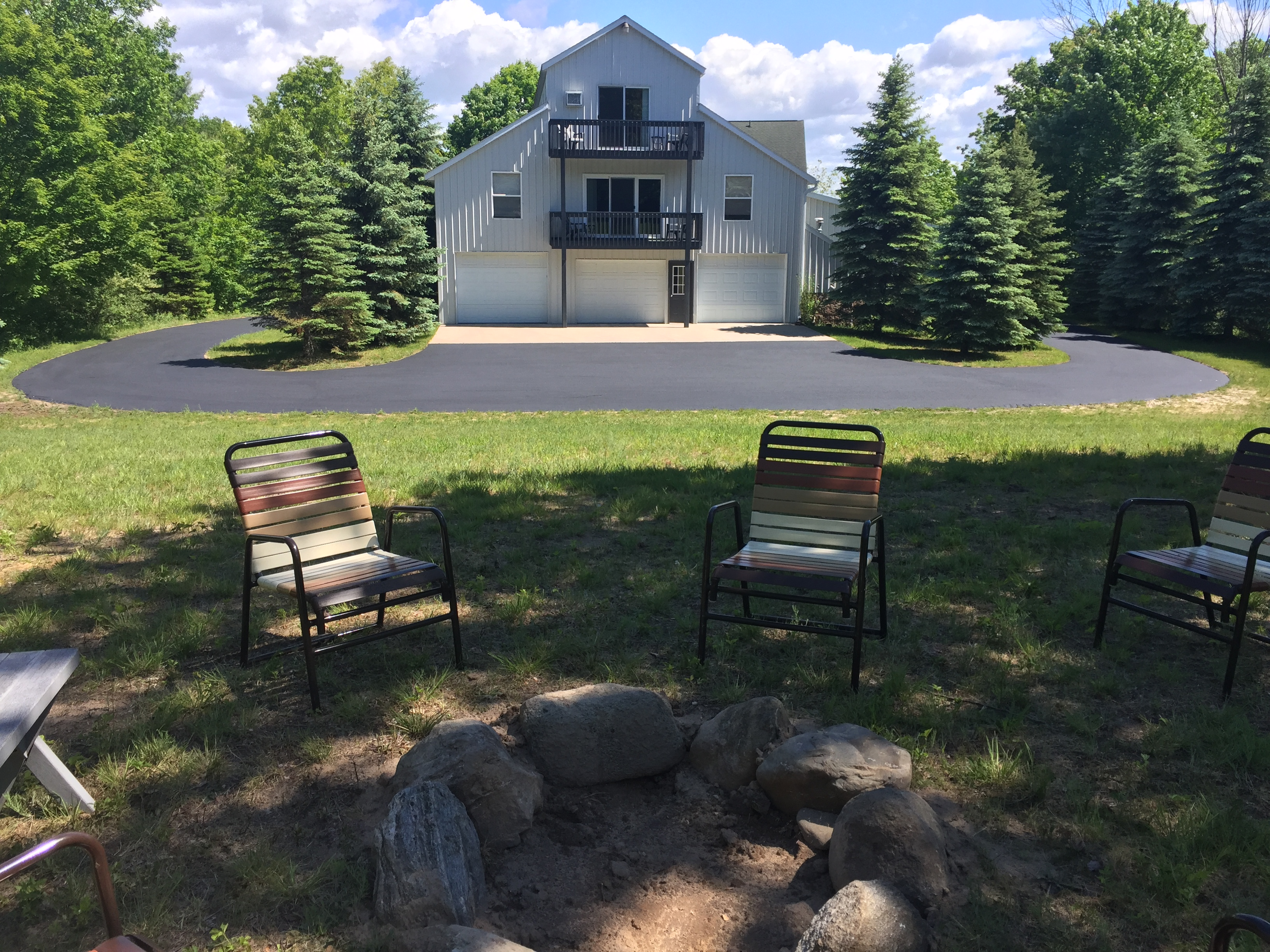View of parking area and fire pit at back Torch Lake lodge. Includes outdoor seating. Yard is available for games. Also shows ample area for parking of toys.