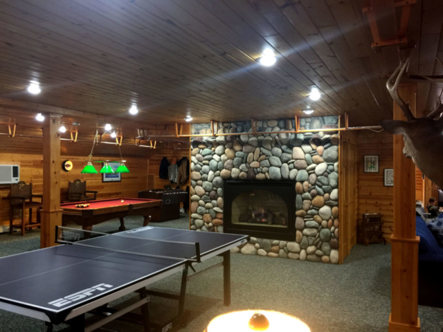 Fireplace, table tennis and pool table at Torch Lake Lodge