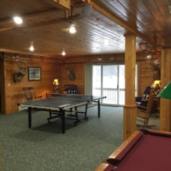 Table tennis and pool table at Torch Lake Lodge. Rear 2nd floor deck in the background viewing fire pit.
