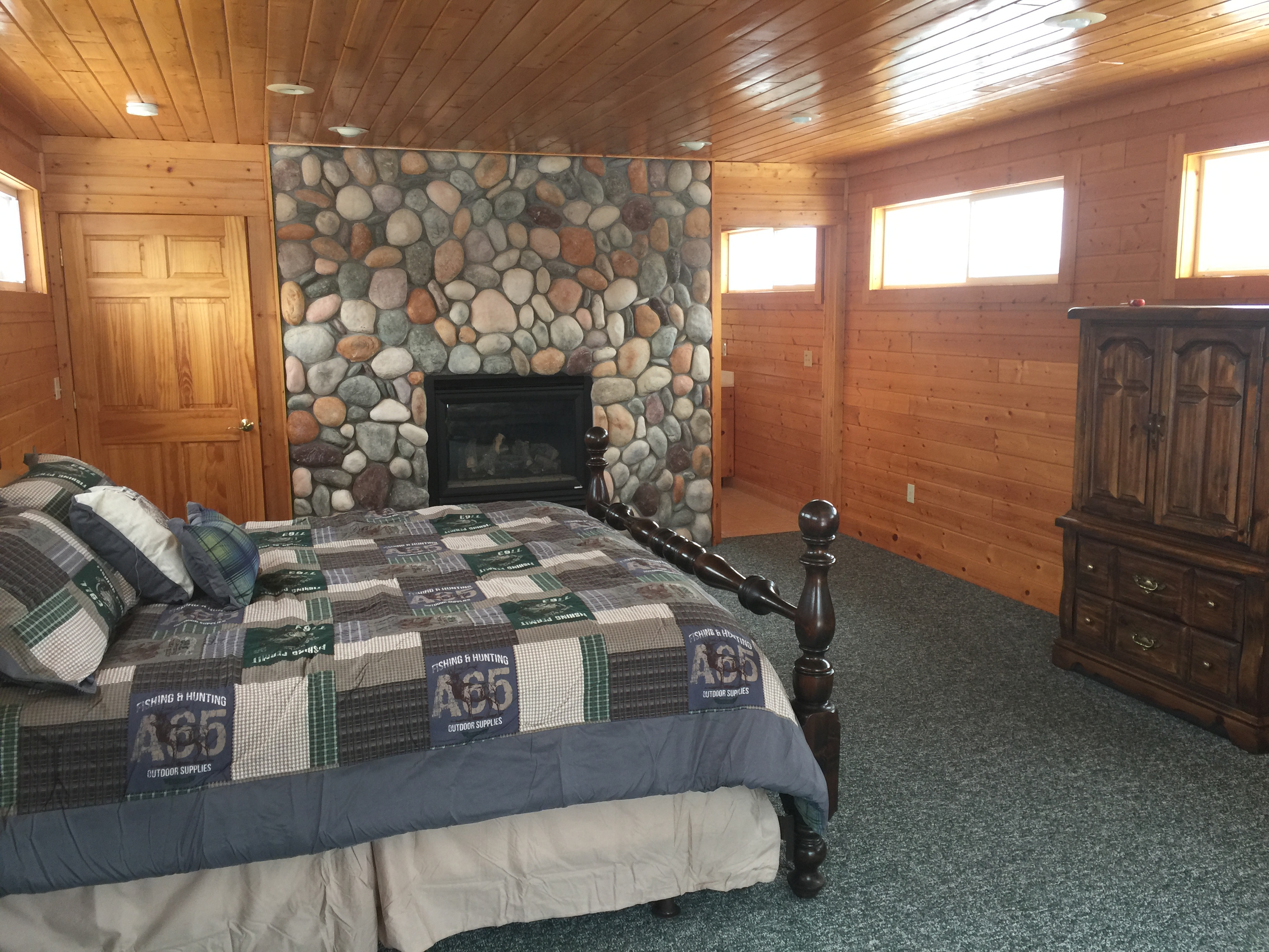 Third floor master bedroom with fireplace and private bathroom, including shower at Torch Lake Lodge. Bedroom includes private deck overlooking trees and fire pit.