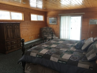 Third floor master bedroom at Torch Lake Lodge. Bedroom includes private deck overlooking trees and fire pit.
